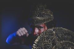 Guerrier barbu d'homme avec le casque en métal et le bouclier, Viking sauvage Photographie stock