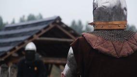 Guerrier courageux dans l'attaque de l'ennemi de attente d'armure en acier sur le champ de bataille pluvieux clips vidéos