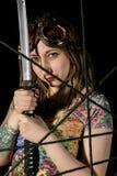 Guerrier gothique féminin en vieux verres pilotes posant avec l'épée de katana Photographie stock libre de droits