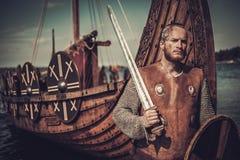 Guerriero di Viking con la spada e lo schermo che stanno vicino a Drakkar sulla spiaggia Fotografie Stock