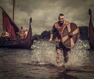 Guerriero di Viking nell'attacco, corrente lungo la riva con Drakkar ai precedenti immagine stock