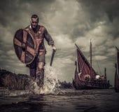 Guerriero di Viking nell'attacco, corrente lungo la riva con Drakkar a fondo immagine stock