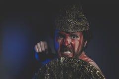 Guerriero medievale e barbuto dell'uomo con il casco del metallo e schermo, selvaggio Immagini Stock