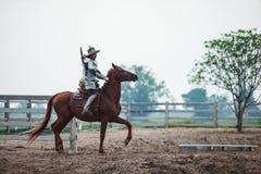 Guerriero tailandese asiatico nel cavallo da equitazione tradizionale del vestito dell'armatura nel fondo rurale dell'azienda agr fotografia stock libera da diritti