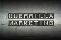 Guerrilla marketing grad. Guerrilla marketing stencil print on the grunge white brick wall Royalty Free Stock Photography