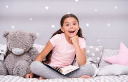 Guess her favorite fairy tale. Girl child sit bed with teddy bear read book. Kid prepare to go to bed. Pleasant time in. Cozy bedroom. Girl kid long hair cute stock images