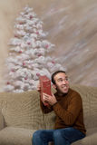 Guess The Present. A young man smiling and shaking his Christmas gift to guess what it is, shot in front of a hand painted background Royalty Free Stock Photos