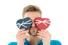 Guess which one. Man holds two heart shaped gift boxes in front of eyes, white background. Macho prepared romantic. Surprise for valentines day. Valentines day Stock Photo