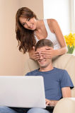 Guess who! Beautiful young women closing her boyfriends eyes wit Royalty Free Stock Photo
