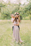 Guess who. Cheerful attractive boyfriend closing eyes of his pretty girl wearing wreath standing in the garden and waiting for him Royalty Free Stock Images