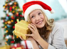 Guessing. Portrait of happy girl holding giftbox and guessing what is inside on Christmas evening Royalty Free Stock Photo