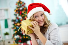 Guessing. Portrait of happy girl holding giftbox and guessing what is inside on Christmas evening Royalty Free Stock Image