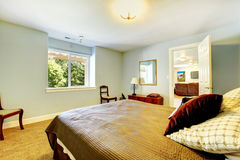 Guest bedroom with blue walls and brown bed. Stock Photo