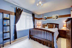 Guest bedroom with periwinkle blue color interior and brown wood Stock Photo
