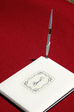 Guest Book. Closed white guest book that says Guests on the front, with a pen standing up on it's side. It is on a red table cloth royalty free stock photography