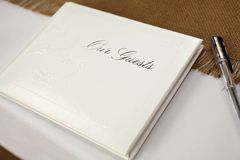 Guest Book. Closed white guest book with a pen on a table at a wedding reception Royalty Free Stock Photography