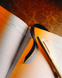 Guest Book and Pen. Gold pen with lined guestbook on wood background Stock Photos