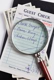 Guest Check and magnifying glass Royalty Free Stock Images