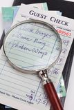 Guest Check and magnifying glass Stock Image
