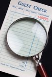 Guest Check and magnifying glass Royalty Free Stock Photos