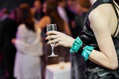 Guest hand and glass with wine at party Royalty Free Stock Photography