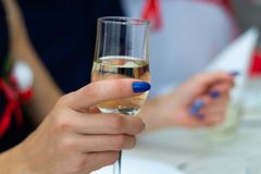 Guest holds glass with bubbly champagne in weddind. Wedding details in close-up view.  royalty free stock photos
