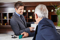 Guest in hotel asking for the way. Senior guest in hotel asking receptionist for the way stock image
