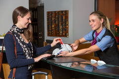 Guest in hotel paying with credit card at reception Stock Photography