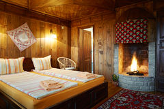 Guest house bedroom with fireplace. Bedroom with fireplace in traditional Bulgarian style rural wooden guest house Royalty Free Stock Images
