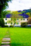 Guest House with Green Lawn and Rocky Path, Norway. Beautiful scandinavian guest house with rocky path and a bright green field, Norway royalty free stock photo