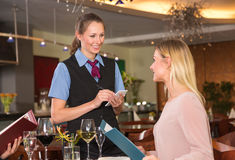 Guest in a restaurant orders meal from menu Stock Image
