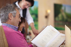 Guest in restaurant reading the menu. Smiling guest in restaurant reading the menu with waitress in background Stock Image