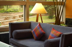 Guest Room Corner. Blue fabric sofa and two pieces of colorful small pillow at the living room corner.  A table lamp and beautiful lawn landscape at the back Stock Image