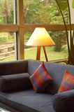 Guest Room Corner. Blue fabric sofa and two pieces of colorful small pillow at the living room corner.  A table lamp and beautiful lawn landscape at the back Stock Photos
