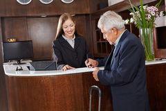 Guest signing form at hotel reception. Senior guest signing a form at the hotel reception counter Royalty Free Stock Photo