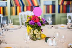 Guest table decorated with gaudy bouquet. Which is in vase vith lemons Stock Photo