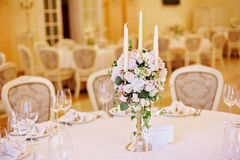 Guest tables with candlestick in rich decorated wedding banquet room. Guest tables with candlestick in luxury decorated wedding banquet room royalty free stock image