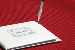 Guestbook. Closed white guestbook that says Guests on the front, with a pen standing up on it's side. It is on a red table cloth Royalty Free Stock Photography