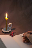 Guestbook. Hand with pen leave guestbook lit flame burning candle stock photo