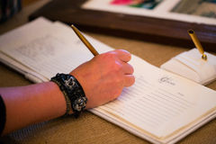 Guestbook Signing. Person signing the guestbook at a wedding ceremony and reception royalty free stock photo