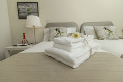 Stylish bedroom and linens in neutral tones. Stylish modern guesthouse bedroom with white towels, neutral color linens and decor royalty free stock photos