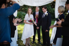 Guests clapping for newly married couple. In park Royalty Free Stock Image