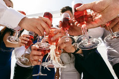 Guests clink glasses  celebration. Guests clink glasses on wedding celebration Stock Image