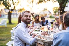 Guests eating at the wedding reception outside in the backyard. Guests sitting at the table and eating at the wedding reception outside in the backyard. A royalty free stock photography