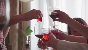Guests raise their glasses to toast the holiday. Group of friends at the table drink alcoholic beverages. Glasses