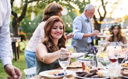 Guests eating at the wedding reception outside in the backyard. Guests sitting at the table and eating at the wedding reception outside in the backyard royalty free stock photography
