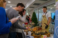 Guests trying wedding dishes from stand. At the exhibition Wedding hassle 2019 took place in Kirov, Russia stock image