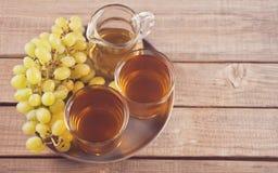 Gug和杯在老木桌上的葡萄汁 免版税库存照片