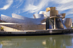Guggenheim Bilbao museum next to the Nervion river. Guggenheim Bilbao museum, by Frank Gehry, next to the Nervion river, with a cloudy blue sky as background Royalty Free Stock Photos