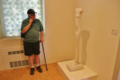 In the Guggenheim Collection, Venice, Italy. Venice, Italy - April 8, 2017: Alberto Giacomettis sculpture Woman Walking or Femme qui marche and a visitor with a Royalty Free Stock Images